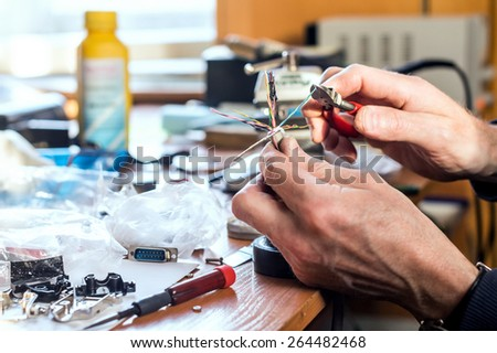 Preparing for soldering by stripping the wire - stock photo