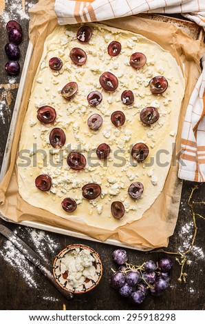 Preparing for tarte flambee flammekueche with grapes and cheese on rustic wooden background, top view - stock photo
