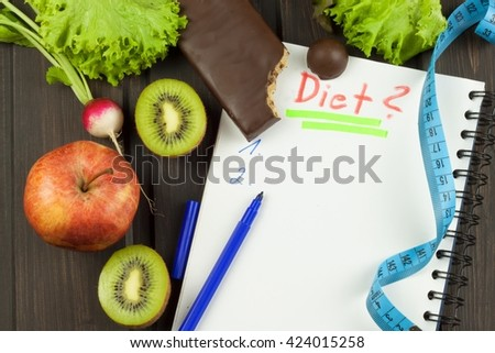 Preparing for the diet program. The decision to initiate dieting. Planning of diet. Notebook measuring tapes and pen on wooden table. - stock photo