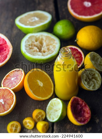 Preparing fresh citrus juice in a rustic kitchen with a bottle of orange juice blend surrounded by halved oranges, grapefruit, blood orange , lime and lemon, some of which have been squeezed