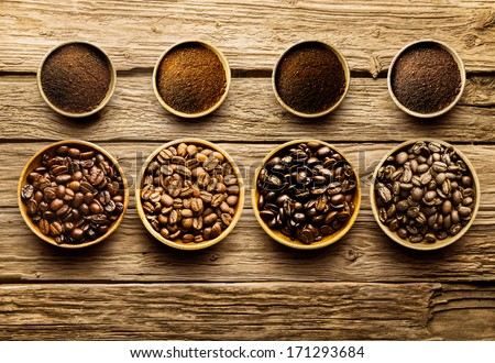 Preparing fresh roast coffee beans to brew with an overhead view of four different varieties of beans with their corresponding ground powder in small dishes on a weathered driftwood background - stock photo