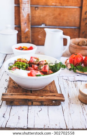 Preparing Fresh vegetarian salad on the ceramic white grand bowl with kitchen dinnerware above from vintage wooden table. Rustic style. See series.  - stock photo