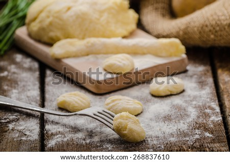 Preparing gnocchi, homemade with fork, all organic, cutting board and desk from wood - stock photo