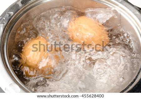 Preparing hardboiled eggs in a steel pan - stock photo