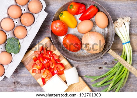 Preparing ingredients for a tasty omelette with a tray of eggs, cheese with diced peppers and a frying pan containing onion, peppers, tomato and spring onions on a wood kitchen counter, overhead view - stock photo