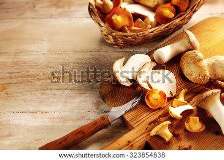 Preparing king oyster mushrooms for use as a cooking ingredient on a wooden chopping board with copyspace and a fresh mushroom border, high angle close up - stock photo