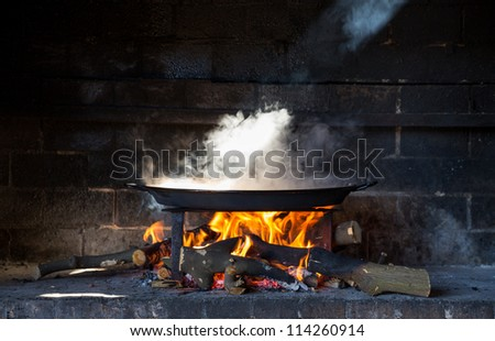 preparing large dish of paella with firewood - stock photo