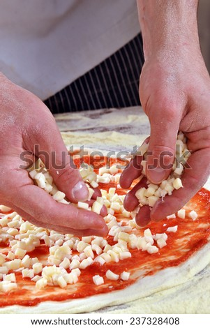 Preparing margarita pizza, adding mozzarella cheese. - stock photo