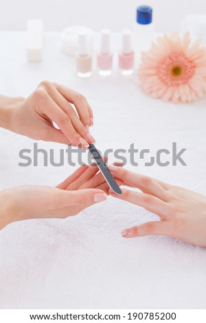 Preparing nails for manicure. Close-up of beautician polishing nails of female customer - stock photo