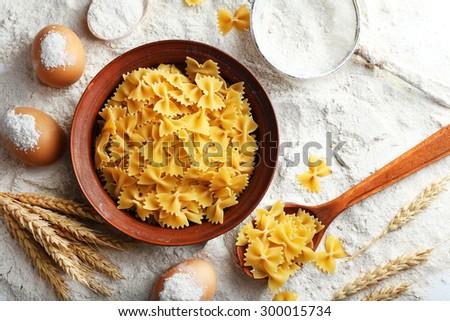 Preparing pasta with white flour and wheat on table, closeup - stock photo
