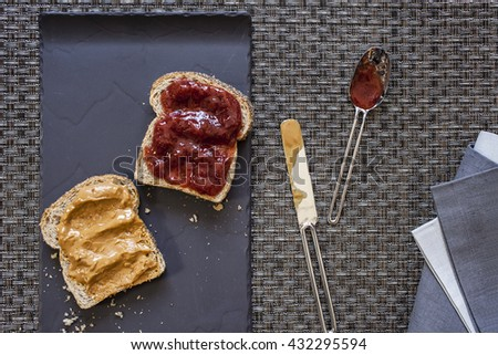 Preparing peanut butter and strawberry jam sandwich on black flat plate with dirty spoon and knife aside and folded blue and gray napkin on wrap textured background - stock photo