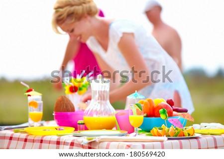 preparing picnic table in summer park - stock photo