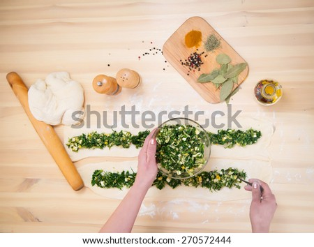 Preparing pie with spinach and feta cheese, food. Cooking pie with green stuffed spinach, eggs and cheese close up on wooden table. Top view. - stock photo