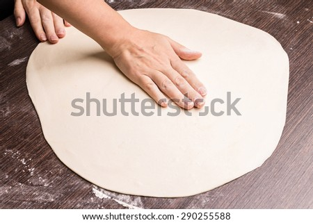 Preparing pizza. Kneading and rolling out dough for baking