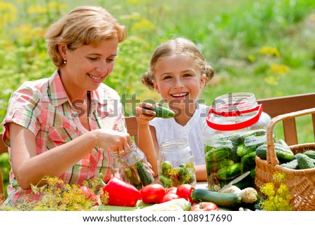 Preparing preserves of pickled cucumbers - girl is helping mother to make preparations of vegetables