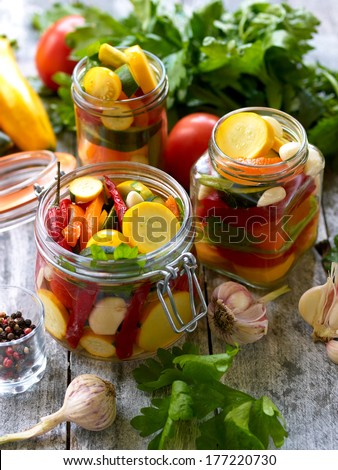 Preparing preserves of pickled zucchini, pepper and tomatoes in jars with spices, garlic and herbs with selective focus - stock photo