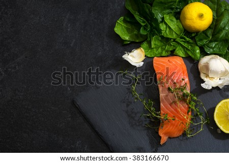Preparing raw salmon fillet with thyme, garlic, lemon and spinach on a dark slate plate, view from above, generous copy space. Vegetarian food concept. - stock photo