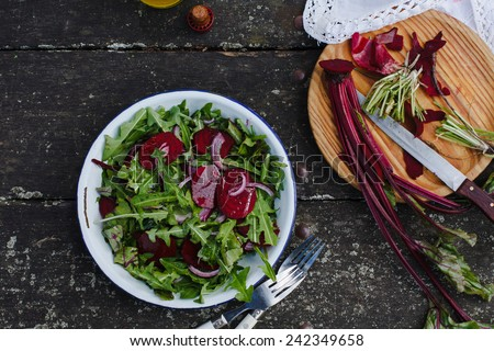 Preparing salad with dandelions, red beets and red onion. Fresh organic vegetables. Food dark background. Healthy herbs from garden  - stock photo