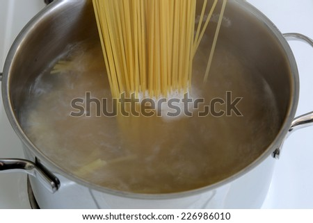 Preparing spaghetti pasta meal: cooking noodles in water in pot - stock photo