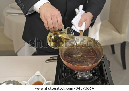 Preparing steak with black pepper sauce on a carving table - stock photo