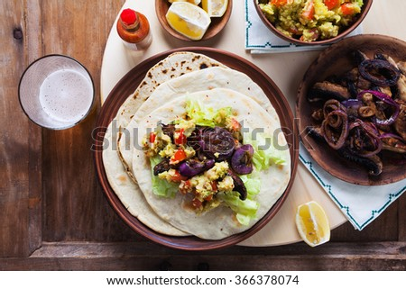 Preparing tasty Tex-Mex tortilla wraps filled with mushrooms, onions, guacamole , overhead view with ingredients . beer. copyspace  - stock photo