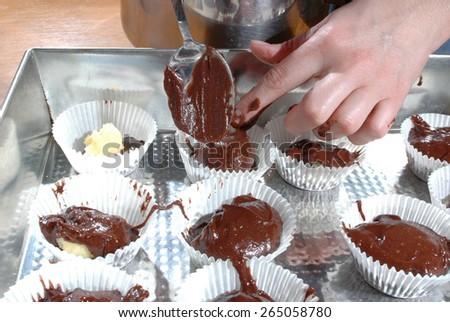 Preparing the cupcakes on the baking tin - stock photo