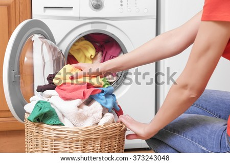 Preparing the wash cycle. Washing machine, hands and clothes. - stock photo