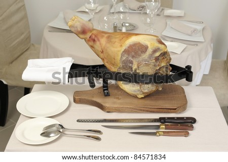 Preparing to carve a raw ham on a ham stand