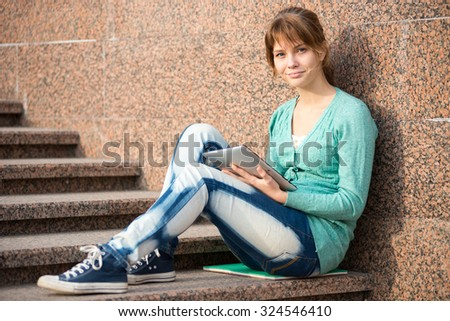 Preparing to exams outdoors. Beautiful young female student writing or reading something from note pad.  Woman sitting on stairs in city park.
