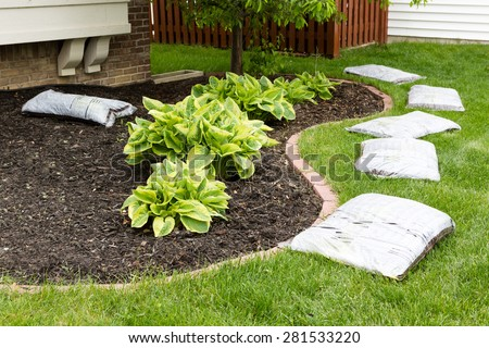 Preparing to mulch the garden in spring laying out a row of commercial organic mulch in bags around the edge of the flowerbed on a neatly manicured green lawn - stock photo