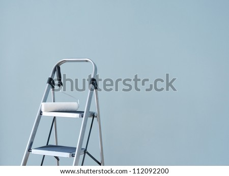 Preparing to paint the wall. Paint roller on a metal ladder. - stock photo