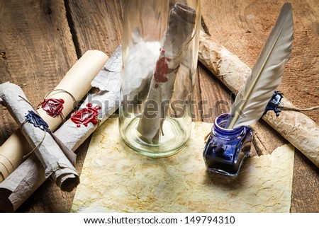 Preparing to send ancient letter in a bottle and writting with blue ink - stock photo