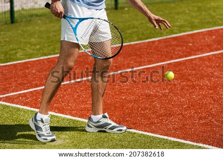 Preparing to serve. Close-up of tennis player preparing to serve a ball  - stock photo