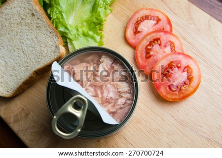 Preparing tuna sandwich, tuna in can opened with bread, lettuce, and tomato on wood background - stock photo