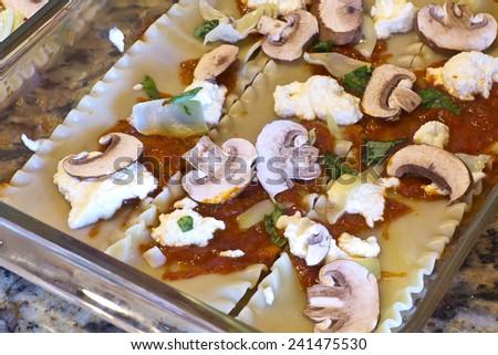 Preparing uncooked lasagna layers to make vegetable lasagna with mushrooms and artichoke hearts - stock photo