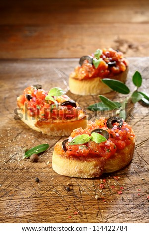 Preparing vegetable bruschetta with finely chopped tomato, onion and seasonings served on slices of crisp golden crusty toasted baguette on a grungy old wooden surface with copyspace - stock photo