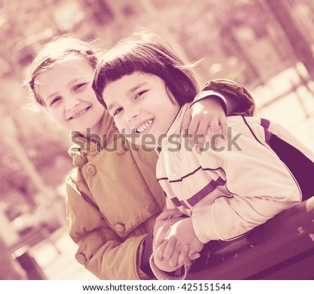 Preschool aged cheerful girls posing in urban street and smiling - stock photo