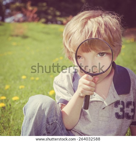 Preschool boy looking through a magnifying glass.  - stock photo