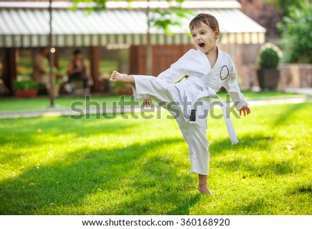 Preschool boy practicing karate outdoors - stock photo