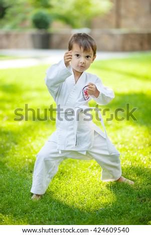 Preschool boy practicing karate outdoors - stock photo