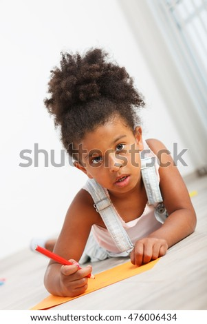 Preschool child girl drawing on the floor