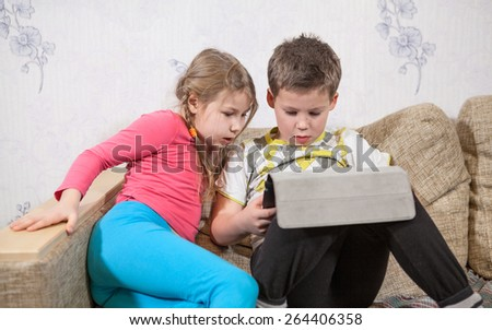 Preschool children having fun with pad while sitting on sofa in domestic room - stock photo