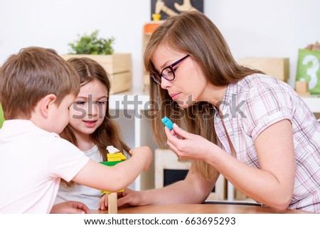 Preschool children in the classroom with the teacher playing