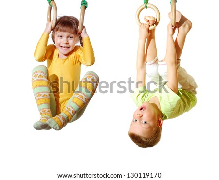 preschool children playing and exercising on gymnastic rings - stock photo