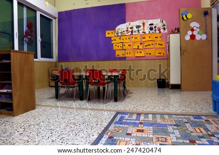 Preschool classroom with red chairs and table with drawings of children hanging on the walls - stock photo