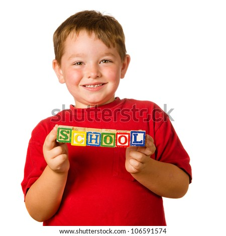 """Preschool education concept with child holding blocks that spell out """"school"""" - stock photo"""