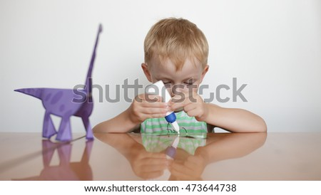 Preschool education. Little boy glues paper on white background.