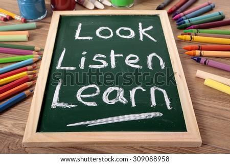Preschool education, Look, Listen, Learn written on small blackboard  - stock photo
