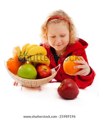 Preschool girl choosing which fruit to eat - stock photo