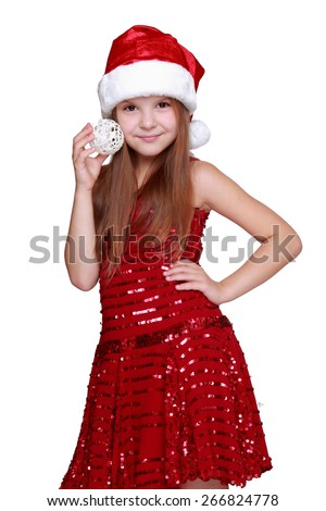 Preschool girl in Santa hat holding Christmas decoration in hands on holiday theme - stock photo